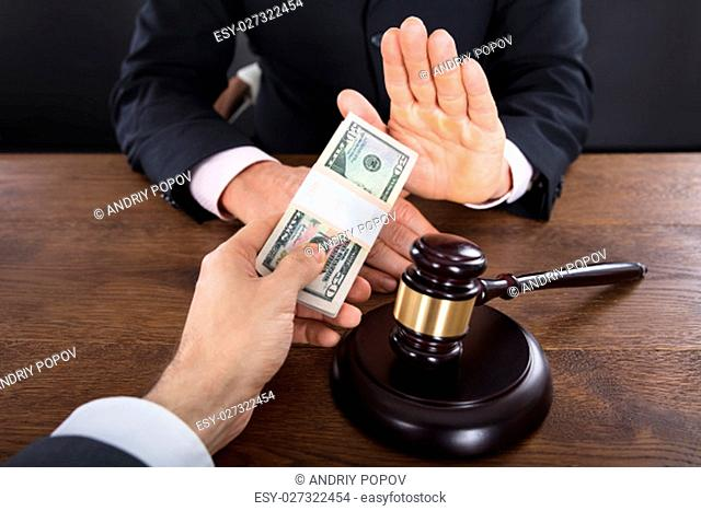 Judge Refusing To Take A Bribe From Client With Gavel On Wooden Desk
