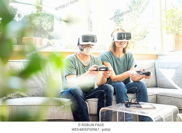 Mature couple sitting on couch at home wearing VR glasses playing video game