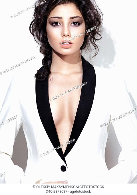 Fashion beauty portrait of a young woman with curly brown hair and beautiful face wearing a stylish white suit, a sexy jacket with open cleavage revealing bare...