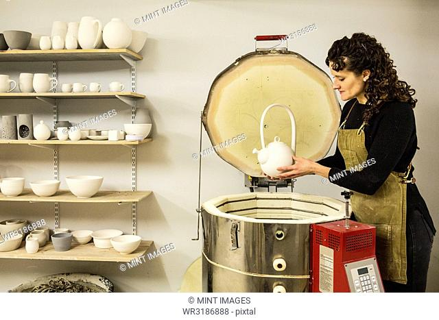 Woman with curly brown hair wearing apron standing in pottery workshop, placing vase into kiln