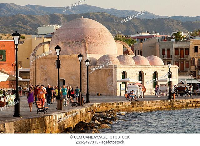 People and horse carriages in front of the Hassan Pasha Mosque at the Venetian harbor near the sea, Chania, Crete, Greek Islands; Greece, Europe