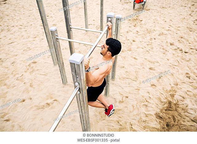 Young man doing chin-ups on the beach