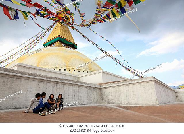 Young people seated and talking in Boudhanath Stupa. Kathmandu. Nepal