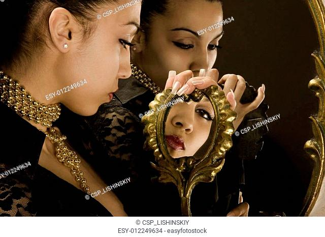 Reflection of the girl in mirrors with an antiquarian frame from gold
