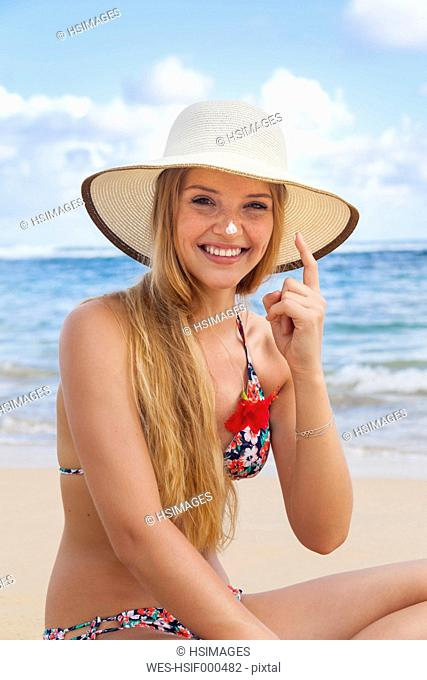 Young woman using sunscreen at beach