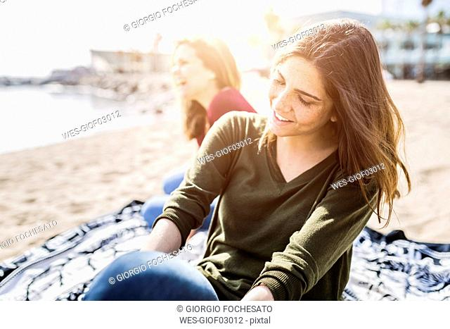 Two happy young women sitting on the beach