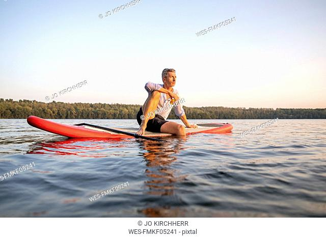 Man sitting on paddleboard on a lake by sunset relaxing
