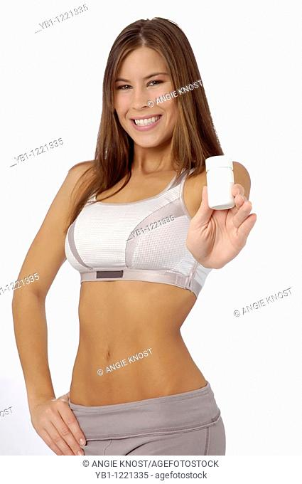 Attractive, fit woman in exercise clothing holding a blank bottle you can add your own product logo here, which could be supplements, vitamins or diet pills