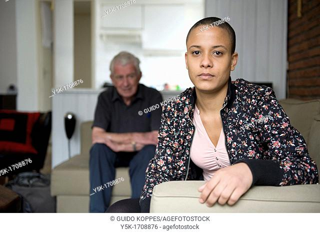 Tilburg, Netherlands. Young African woman, with her father in the background, sitting in her living-room