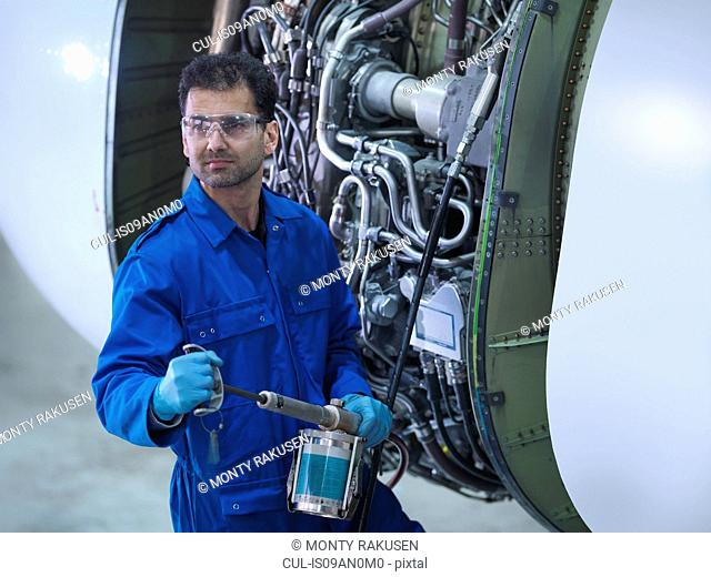 Engineer working on jet engine in aircraft maintenance factory, portrait