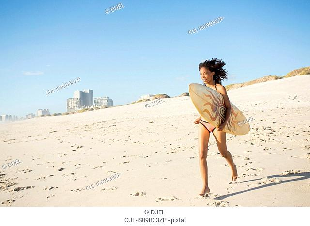 Young female surfer running on beach, Cape Town, Western Cape, South Africa