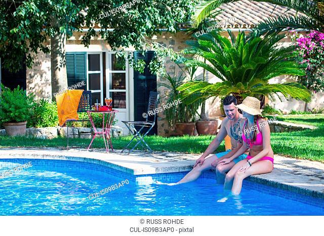 Couple sitting on poolside