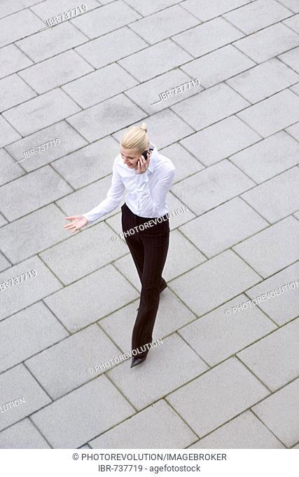 Businesswoman talking on phone as she walks