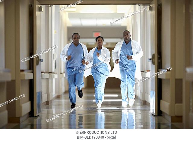 African American medical professionals running in hallway