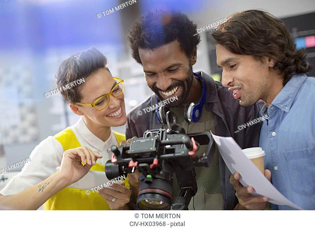 Smiling journalists and cameraman using digital camera