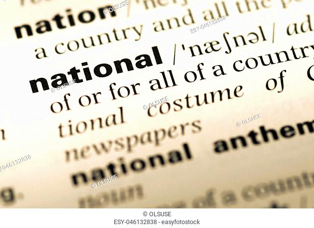 Close up of old English dictionary page with word national