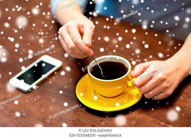 drinks, people, technology and lifestyle concept - young woman with smartphone drinking coffee at cafe over snow