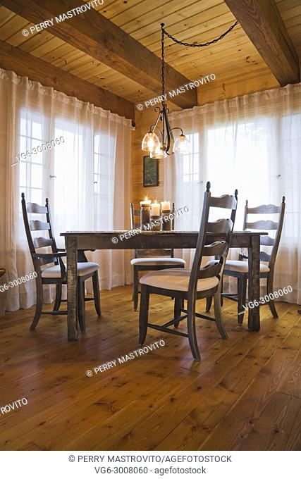 Lit candles on top of brown wooden dining table with white cloth upholstered high-back chairs in the dining room inside a small cottage style log home, Quebec