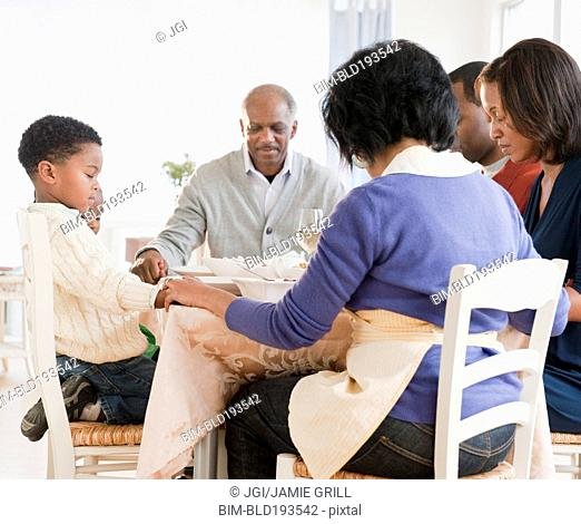 African American family praying before meal