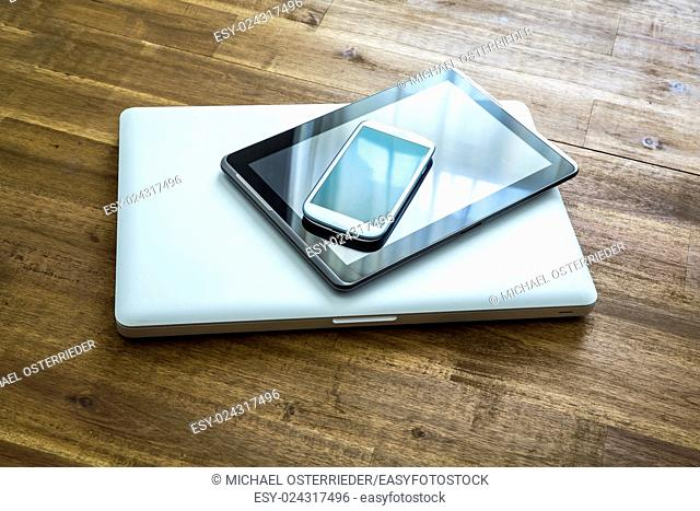 A Laptop computer, a Tablet PC and a Smartphone on a wooden Desktop. .