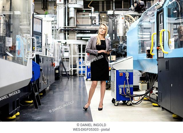Woman with tablet at machine in factory shop floor lookig around