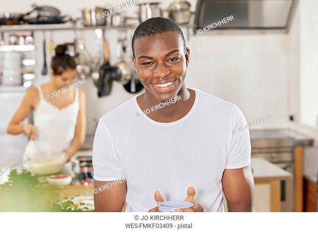 Portrait of happy young man with coffee mug in kitchen