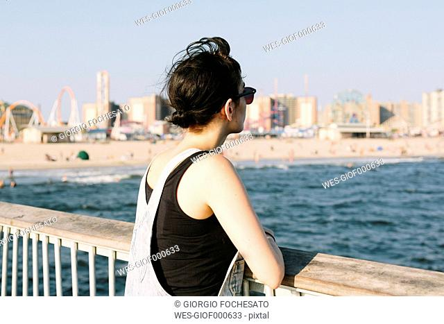 USA, New York, Coney Island, young woman relaxing on pier