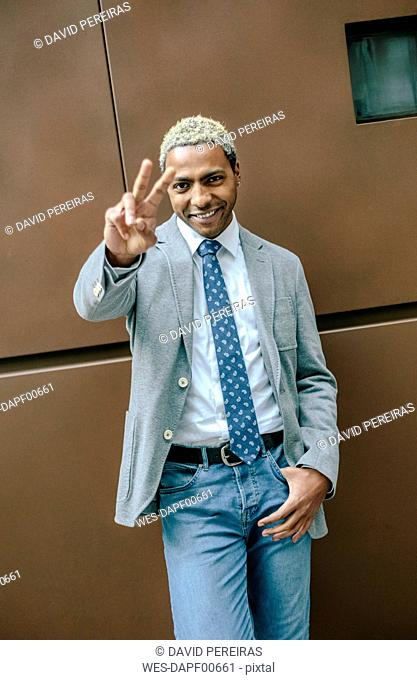 Businessman standing in front of wall making hands gestures