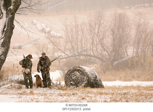 Hunters waterfowl hunting Near Hay Bales in Winter