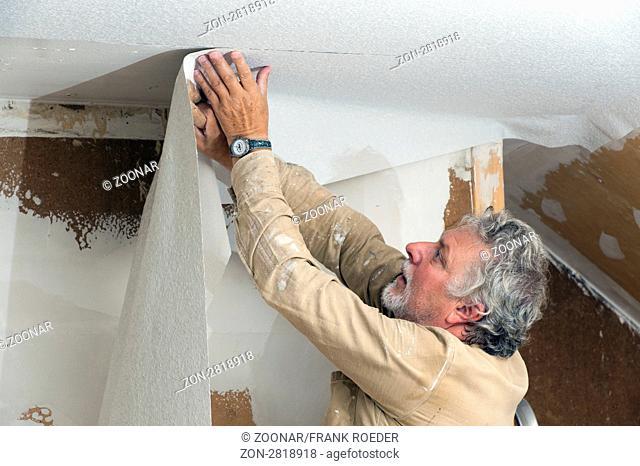 Handwerker beim Tapezieren der Zimmerdecke