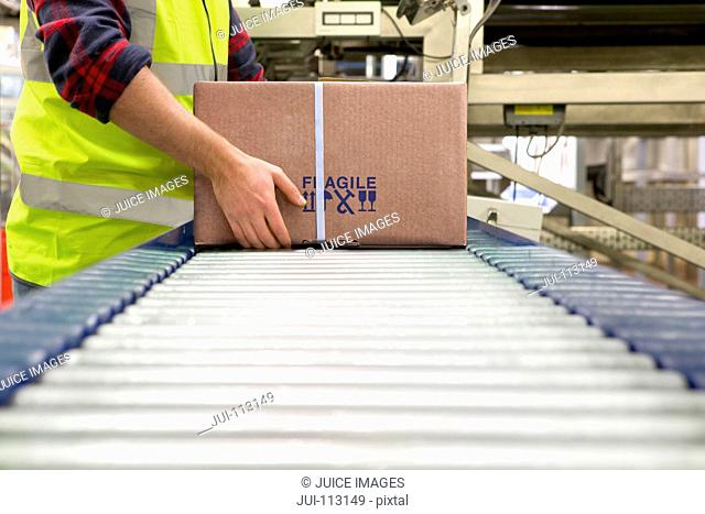 Worker processing cardboard box on conveyor belt in distribution warehouse
