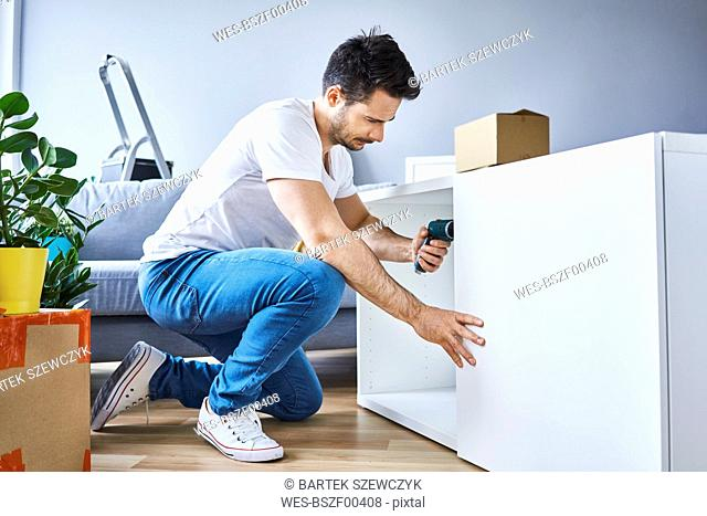 Man assembling a bookshelf in new apartment