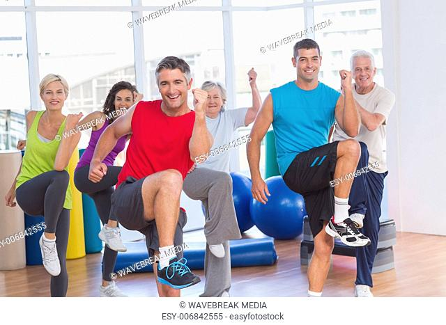 People performing aerobics exercise in gym class