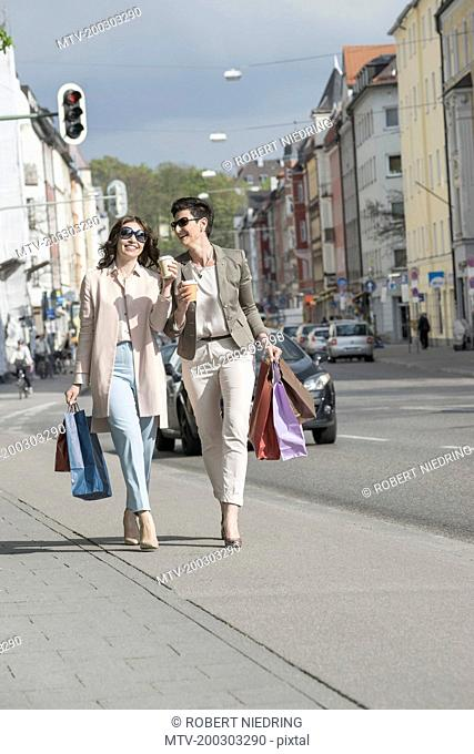 Two mature women shopping in the city with coffee, Bavaria, Germany