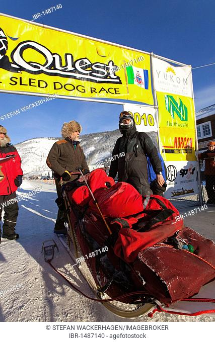 Dog musher Normand Casavant standing with his loaded sled, talking to race marshal Hans Oettli after arriving in Dawson City, Yukon Quest 1