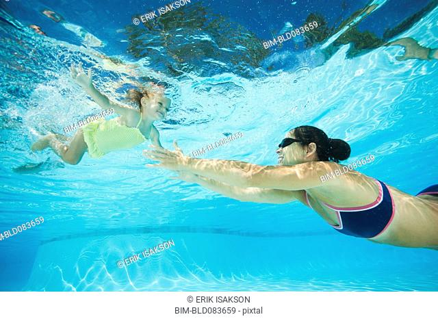Mother swimming in swimming pool with daughter