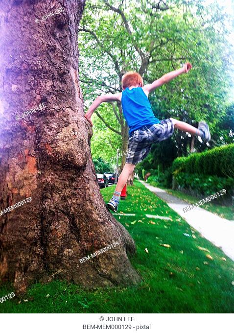 Caucasian boy playing on tree