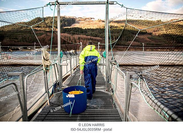 Worker at salmon farm in rural lake