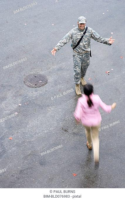 Woman running to soldier with arms outstretched