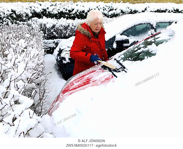 Woman clearing car from snow in Ystad, Scania, Sweden, North Europe