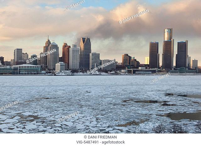 Smoke from a fire in an abandoned neighbourhood wafts behind the skyline of downtown Detroit, Michigan, USA. Chunks of ice can be seen floating along the...