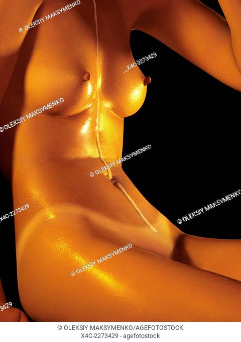 Nude woman with milk running down her shiny naked body
