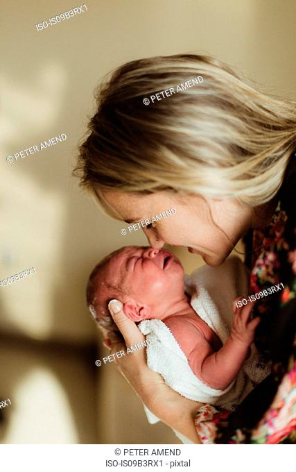 Mid adult woman nose to nose with newborn baby daughter