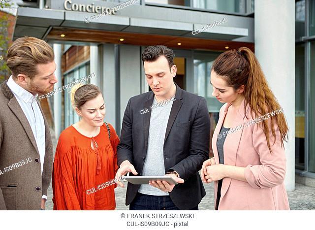 Businesswomen and businessmen looking at digital tablet outside office, London, UK