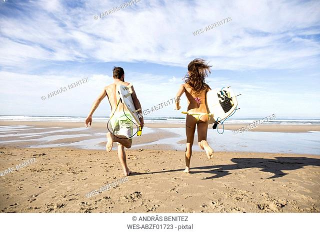 Couple carrying surfboards running on the beach