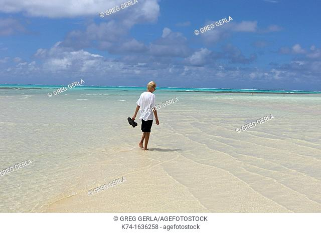 young man walking along a beach
