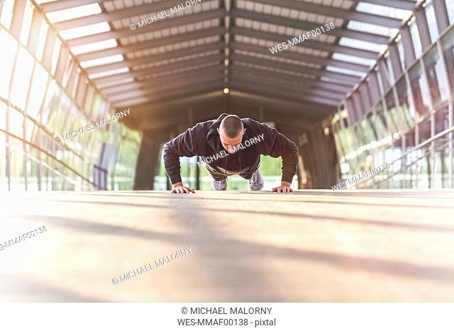 Young man doing push-ups on a bridge