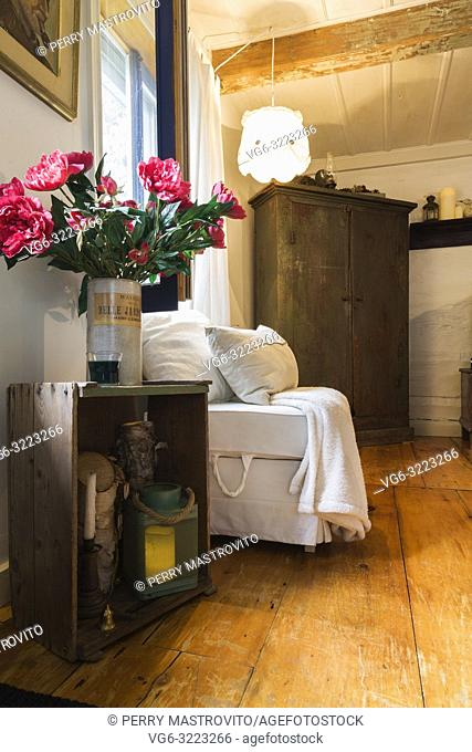 Old wooden crate table, with pink silk flowers in vase, armless white upholstered sitting chair and antique wooden armoire in living room inside an old 1862...