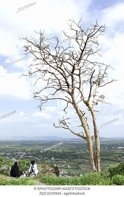 DAULATABAD, MAHARASHTRA, INDIA, August 2018, Women resting under a dried tree