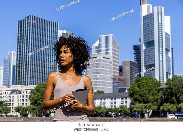 Germany, Frankfurt, portrait of young woman with tablet in the city
